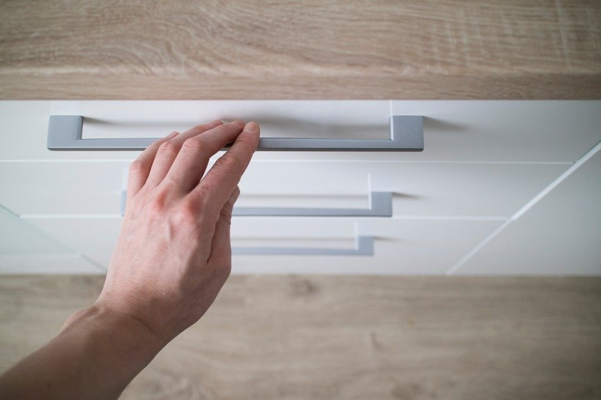 detail man hand is open of a laminate stylish kitchen drawer