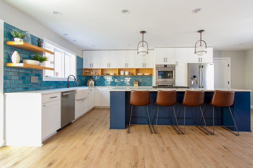 Delafield kitchen with navy island and blue subway tile backsplash