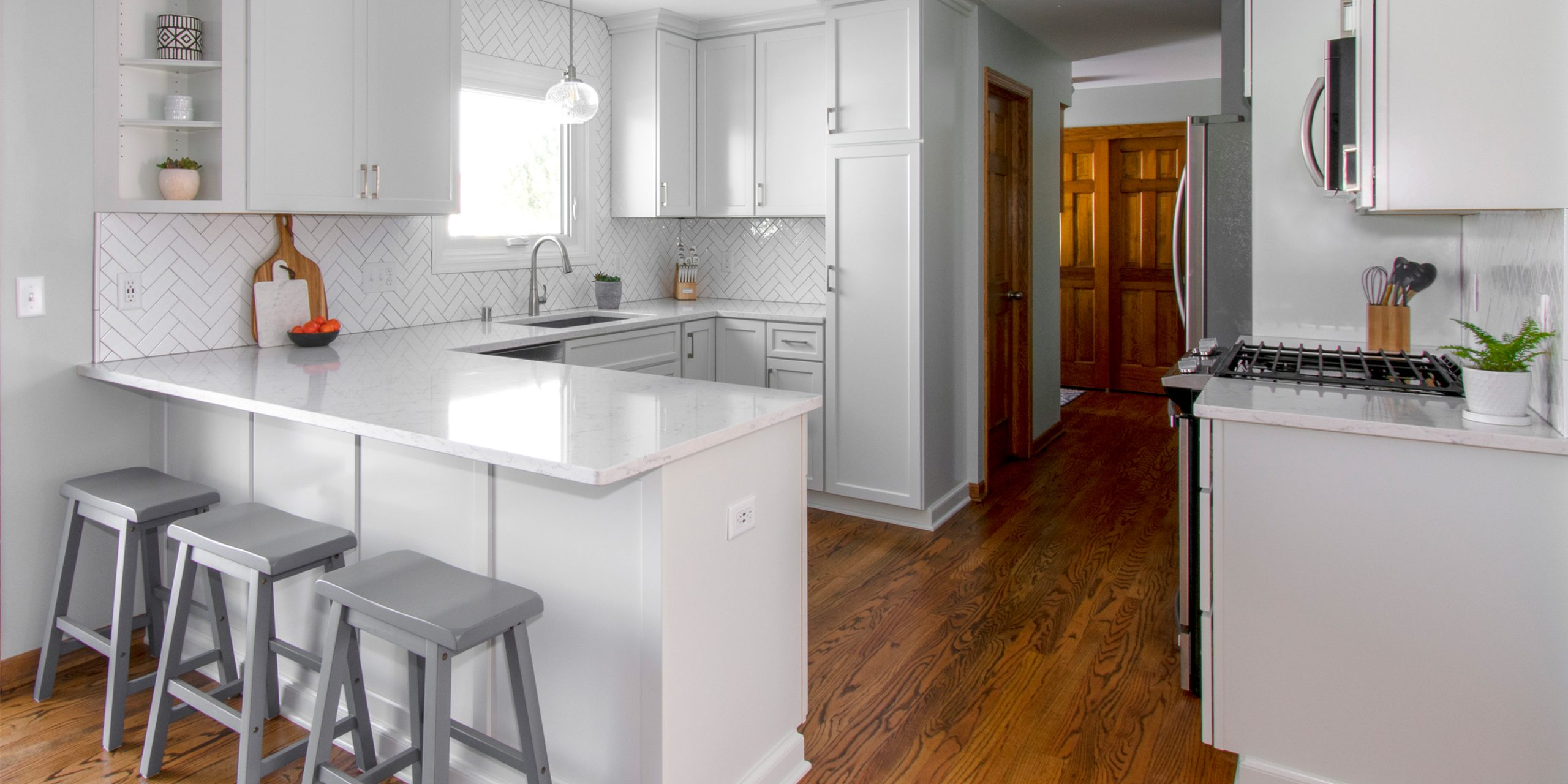 Waukesha kitchen remodel with white cabinets, counters, herringbone backsplash, pendant light, hardwood floors