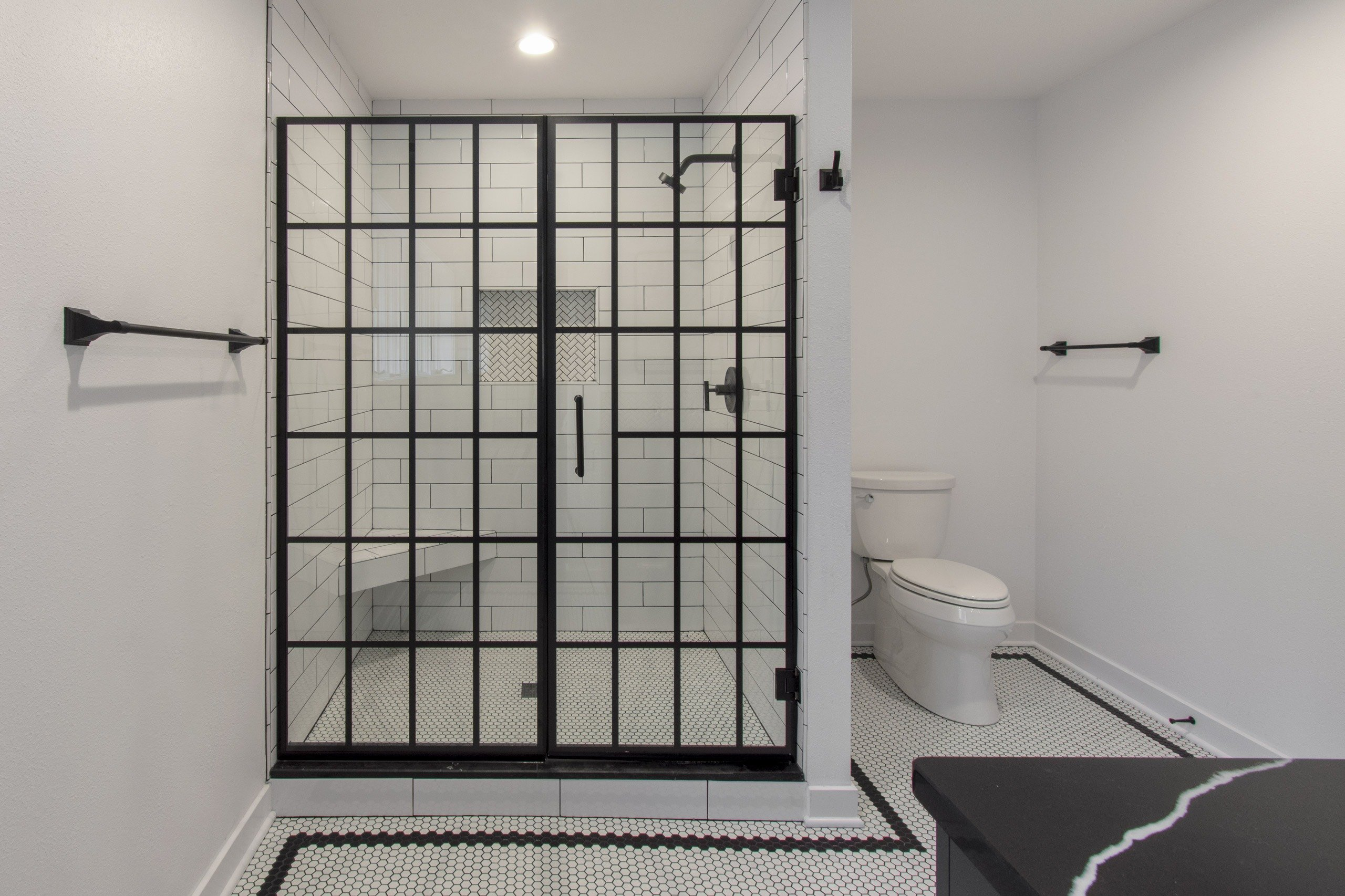 Delafield classic black and white master bathroom with subway tile glass shower door and hexagon tile floor