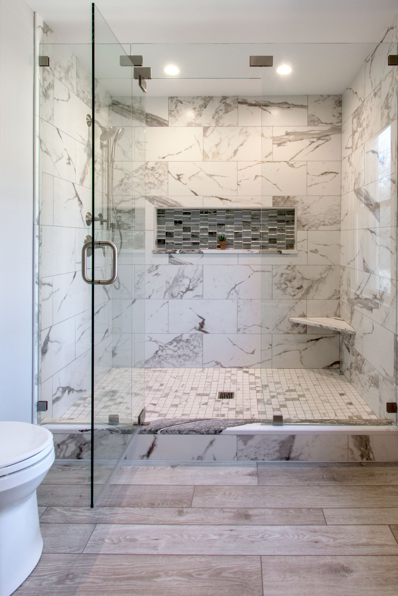 Big walk in glass shower with marble look porcelain tile and mosaic niche