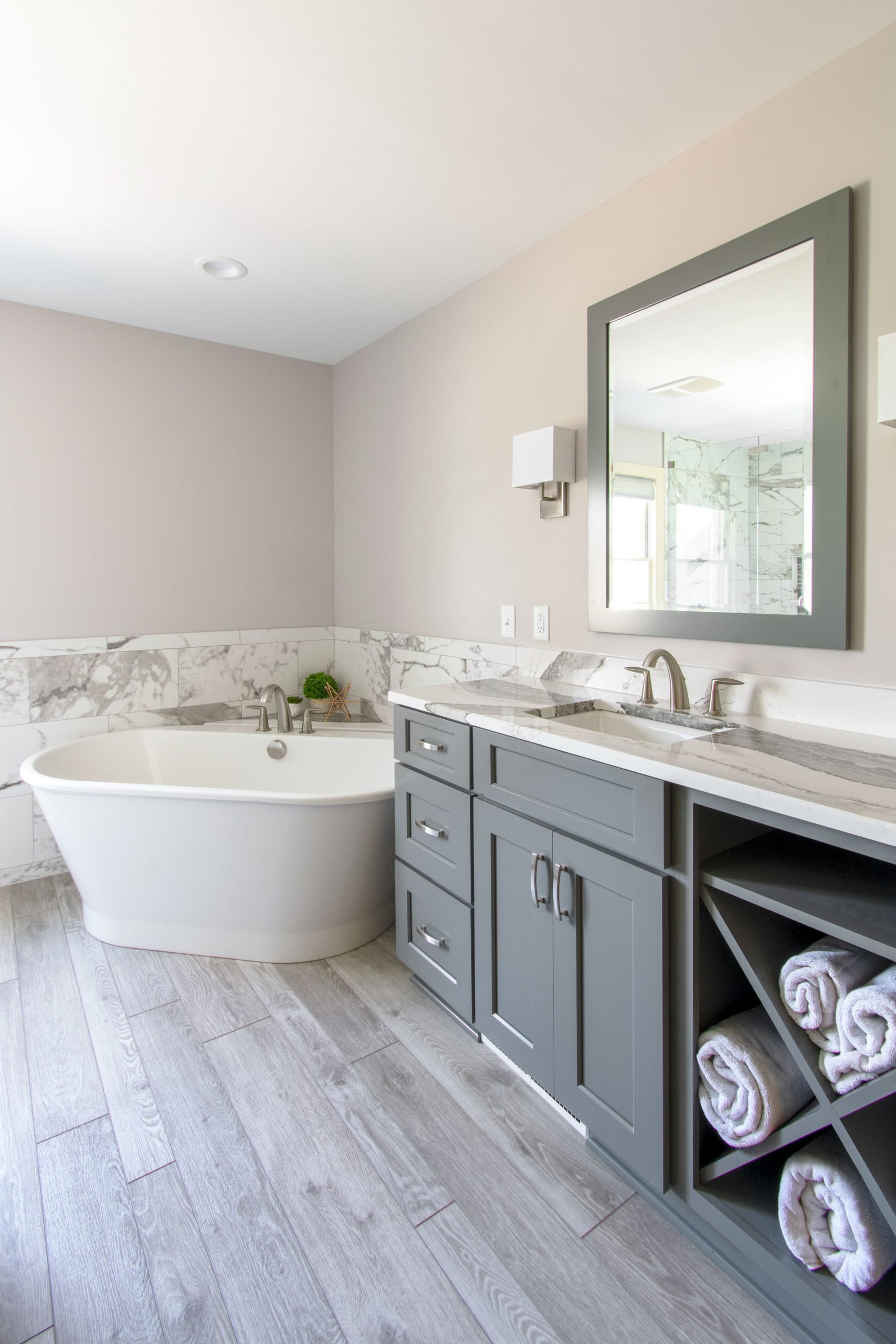 Luxurious master bathroom gray vanity, gray mirror and Maxx bathtub