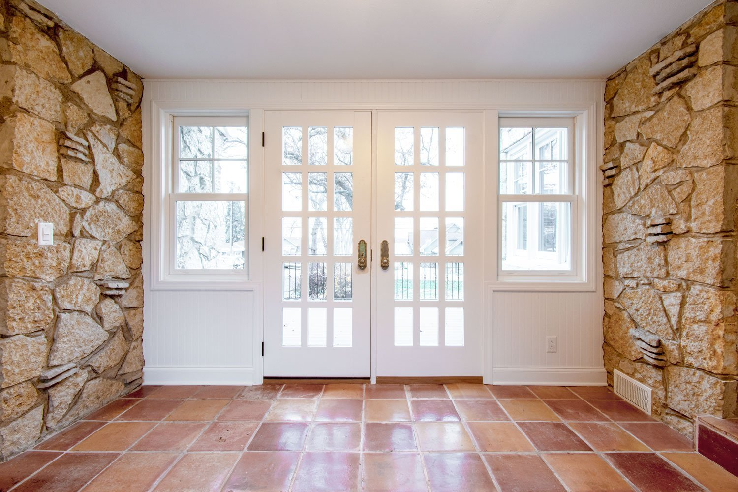 Delafield Breezeway double doors with tile floor and lannon stone walls