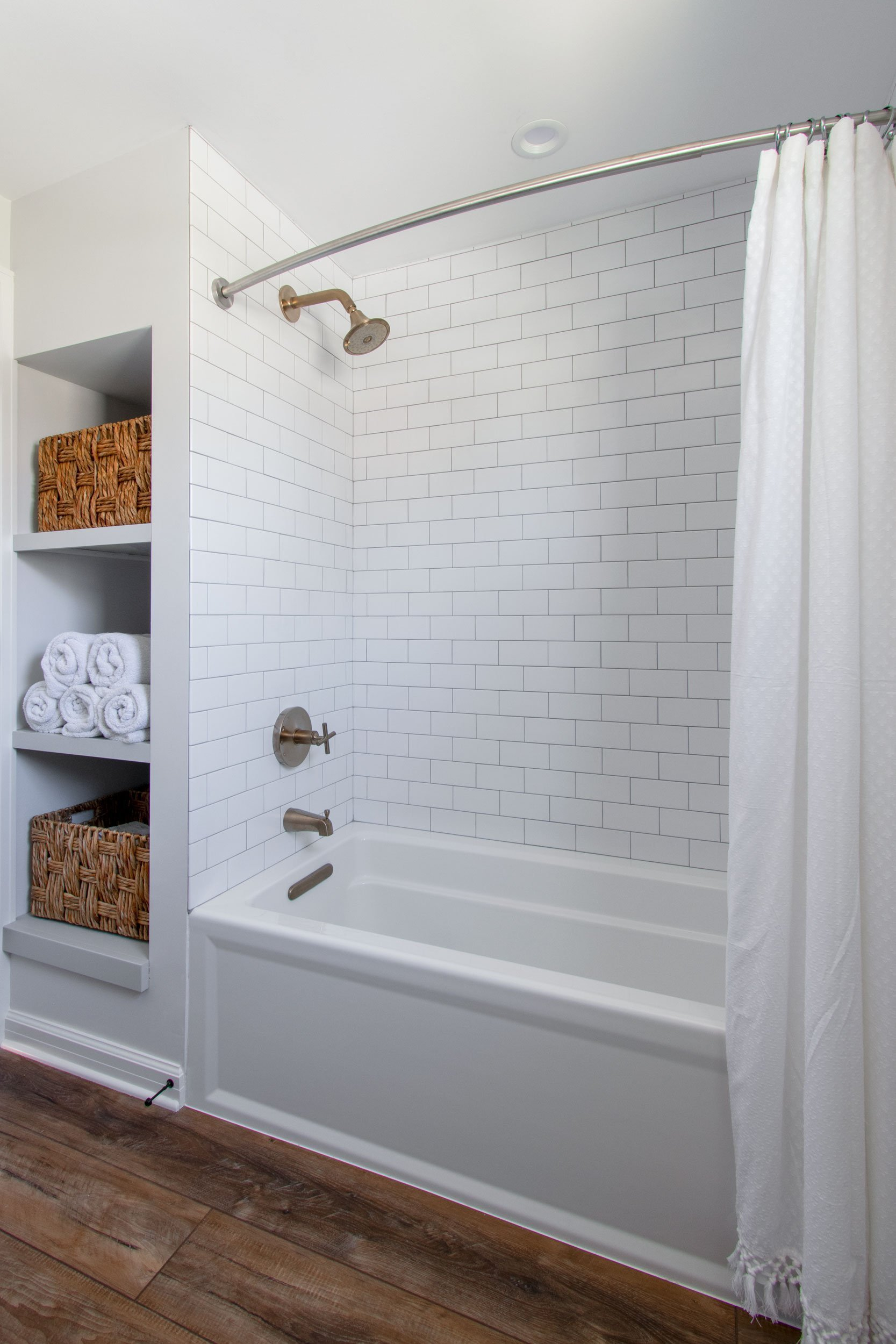 Bathtub with subway tile, bronze fixtures and open shelving