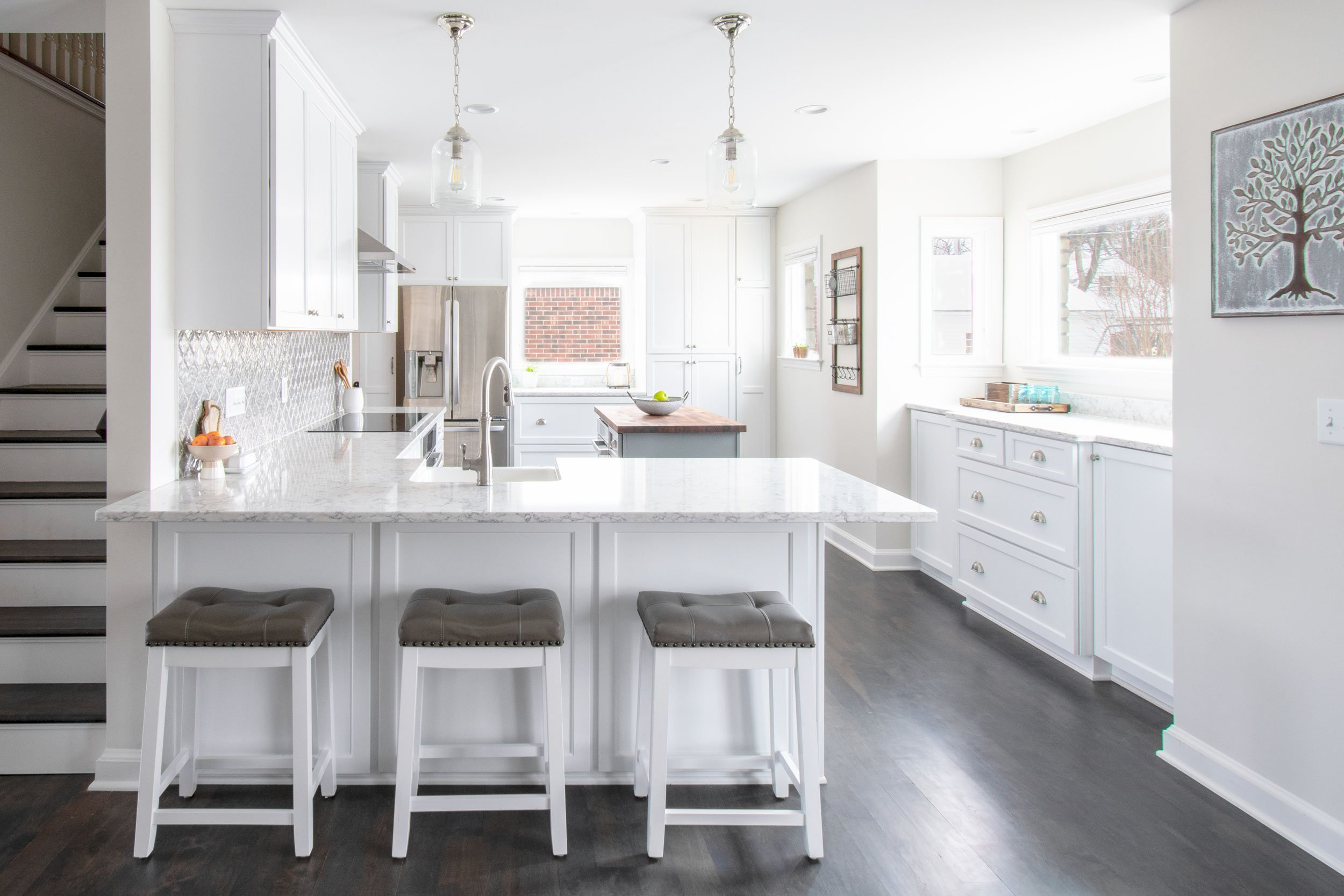 Open concept kitchen with white cabinets and peninsula