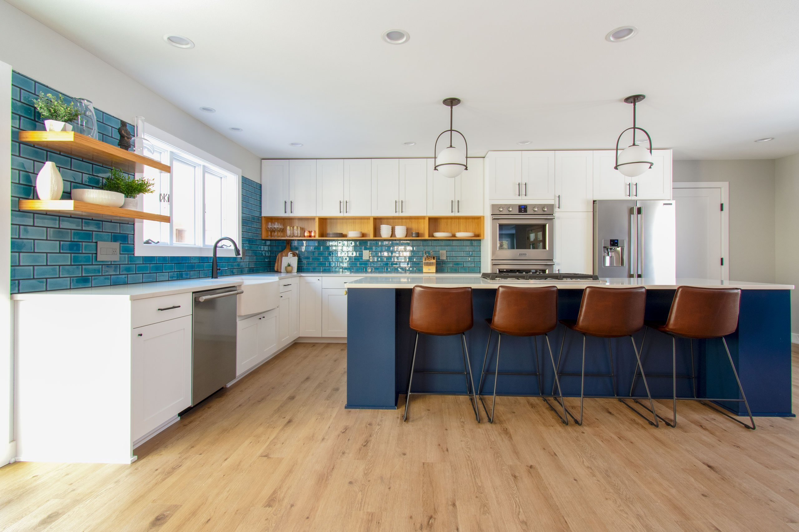 Contemporary white kitchen with blue backsplash and navy island