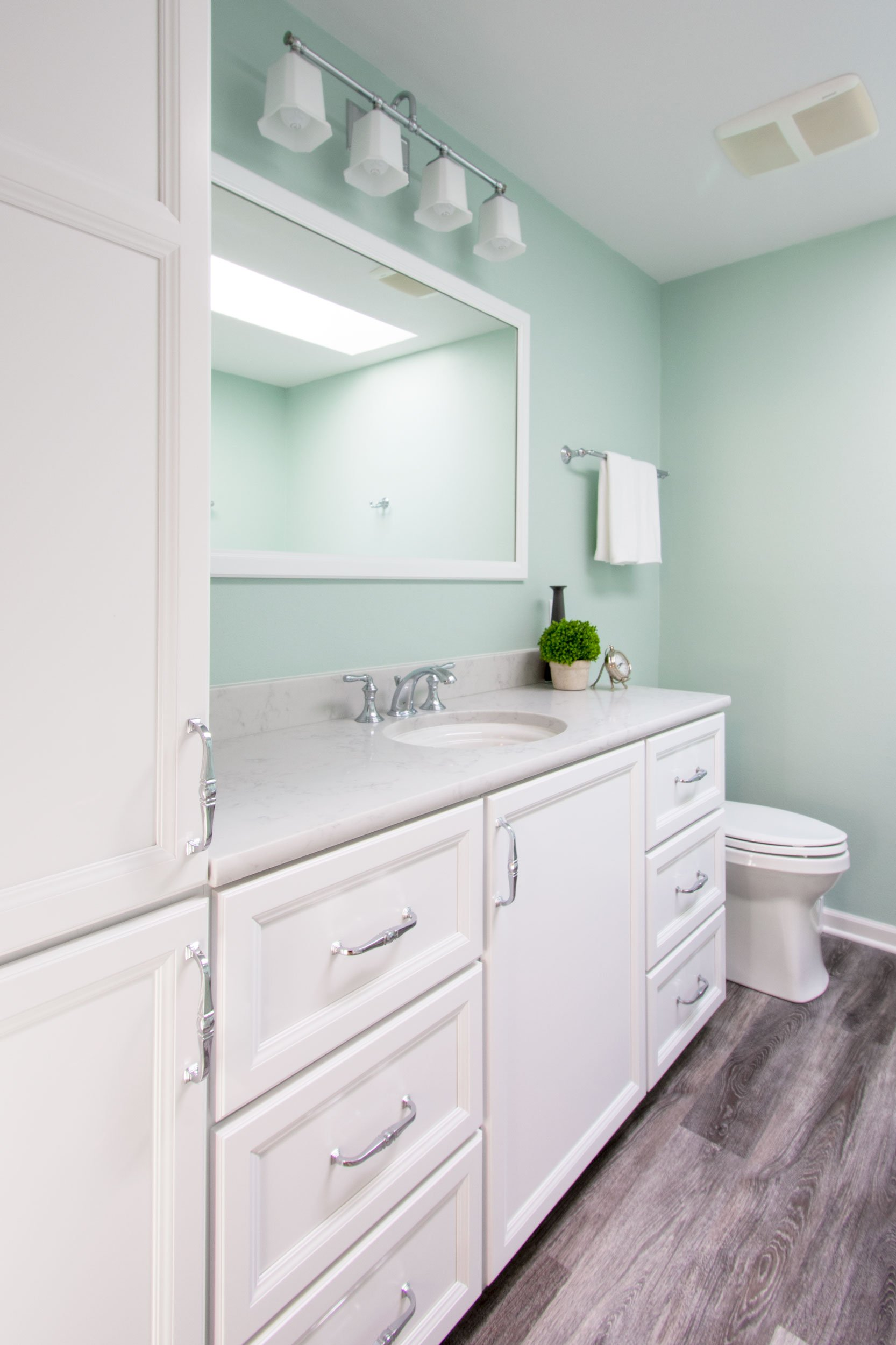 Bright and airy master bathroom with white vanity and linen cabinet