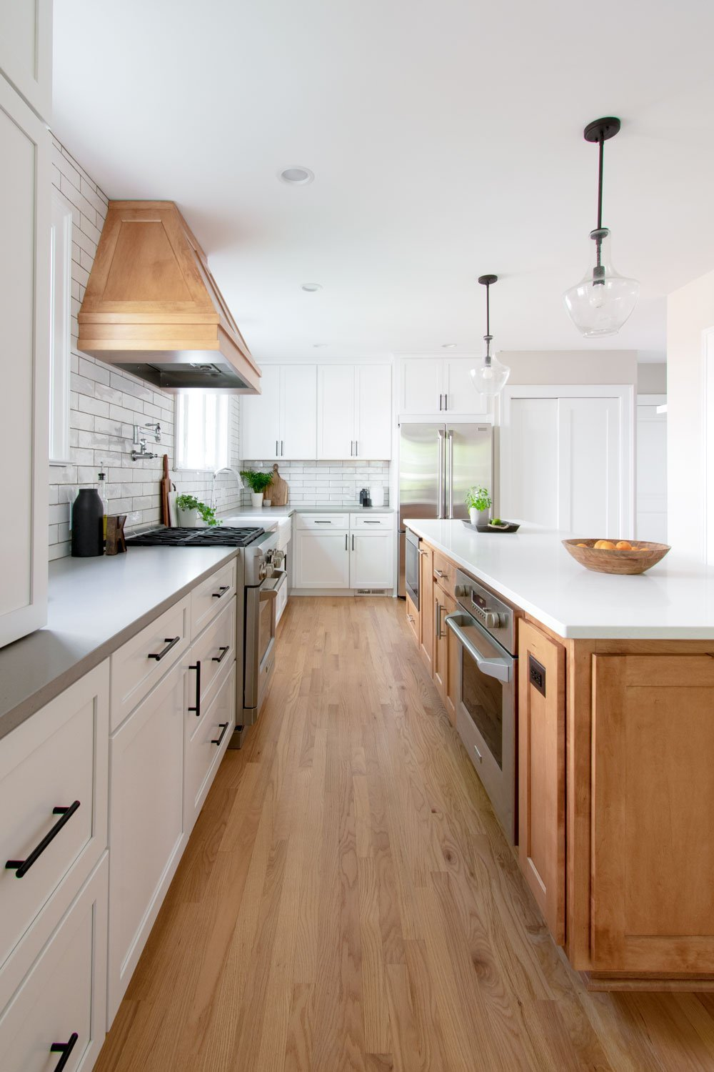 Open concept kitchen with white shaker cabinets and wood island