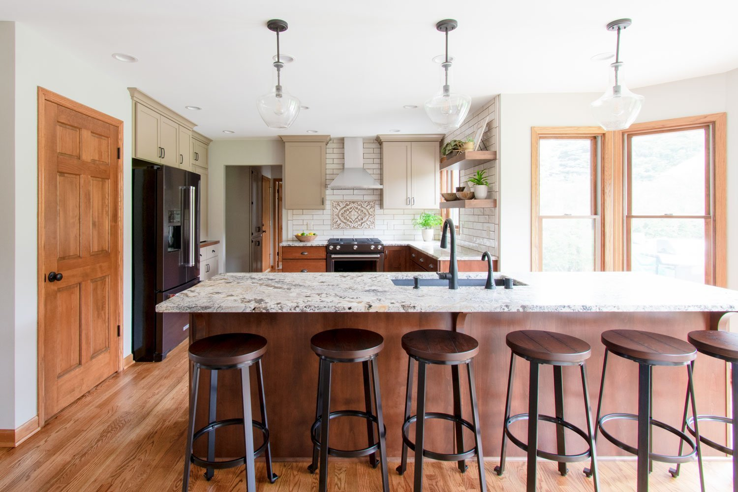 open concept kitchen with leathered granite counters, wood island and taupe upper cabinets