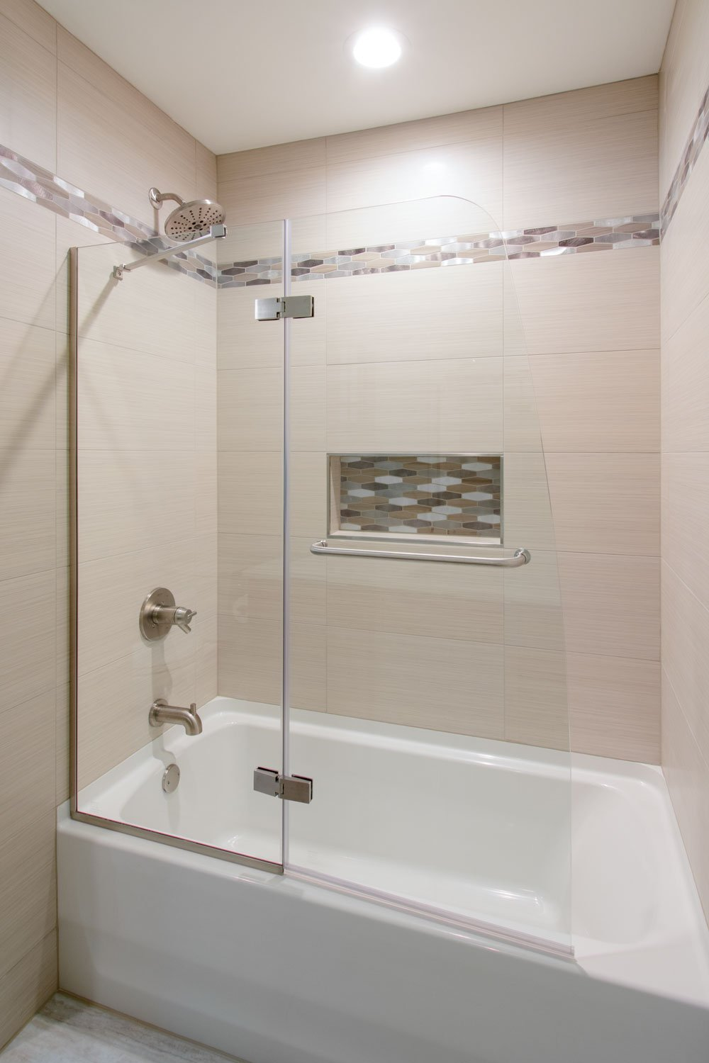 tiled shower with mosaic accent and glass door