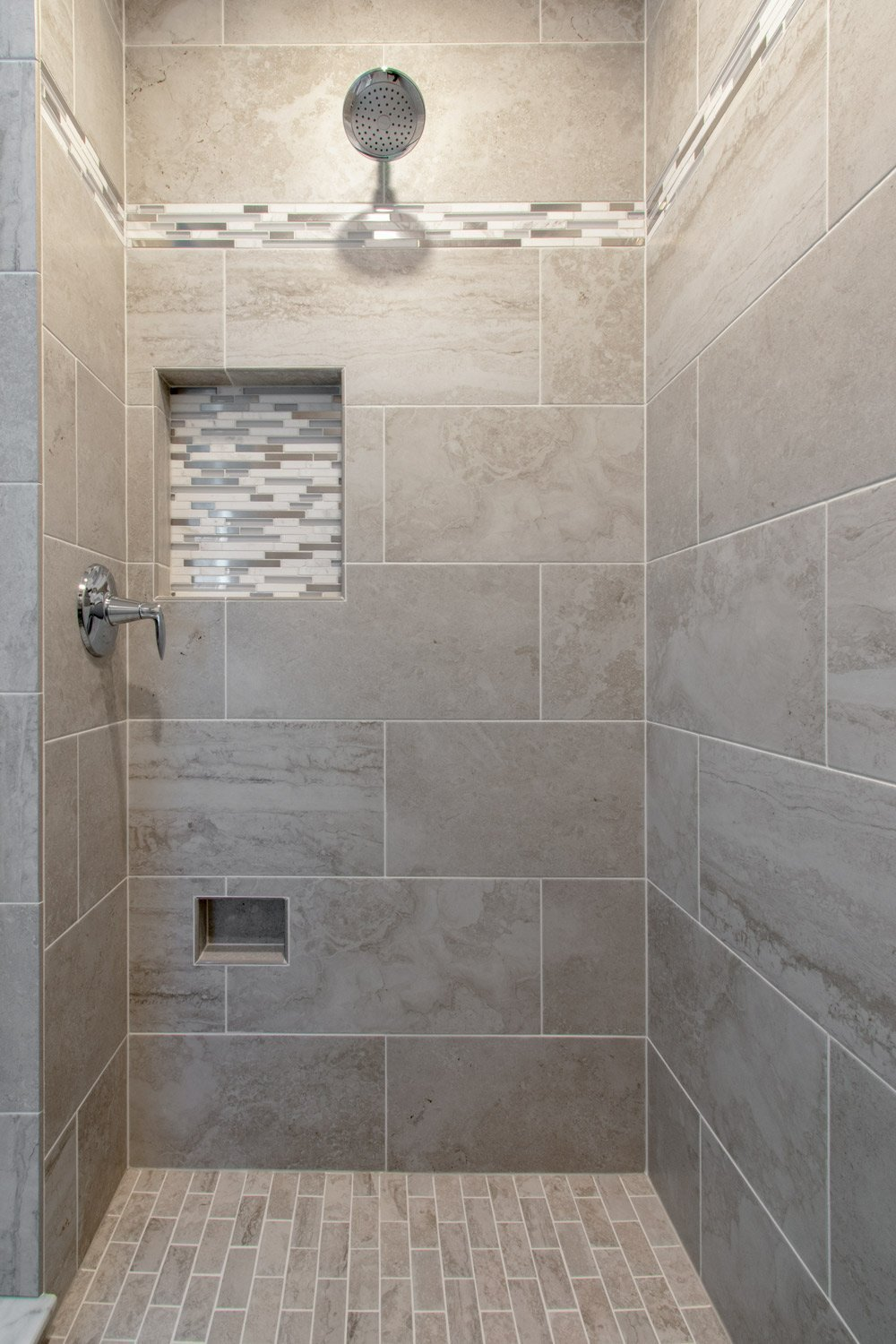tiled walk in shower with mosaic tile in niche