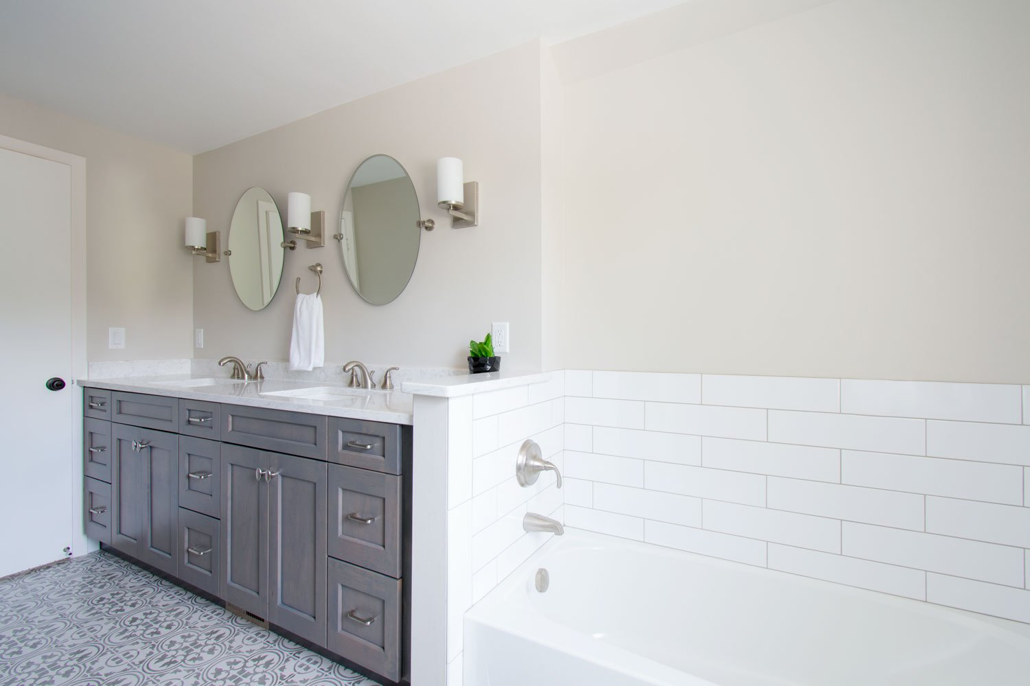 Subway tile wall bathtub and wood cabinetry