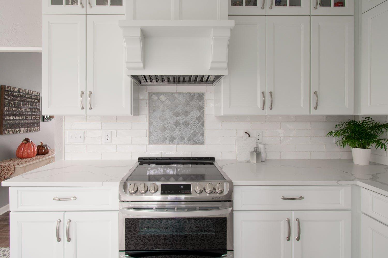 subway tile backsplash with tile plaque accent behind stove