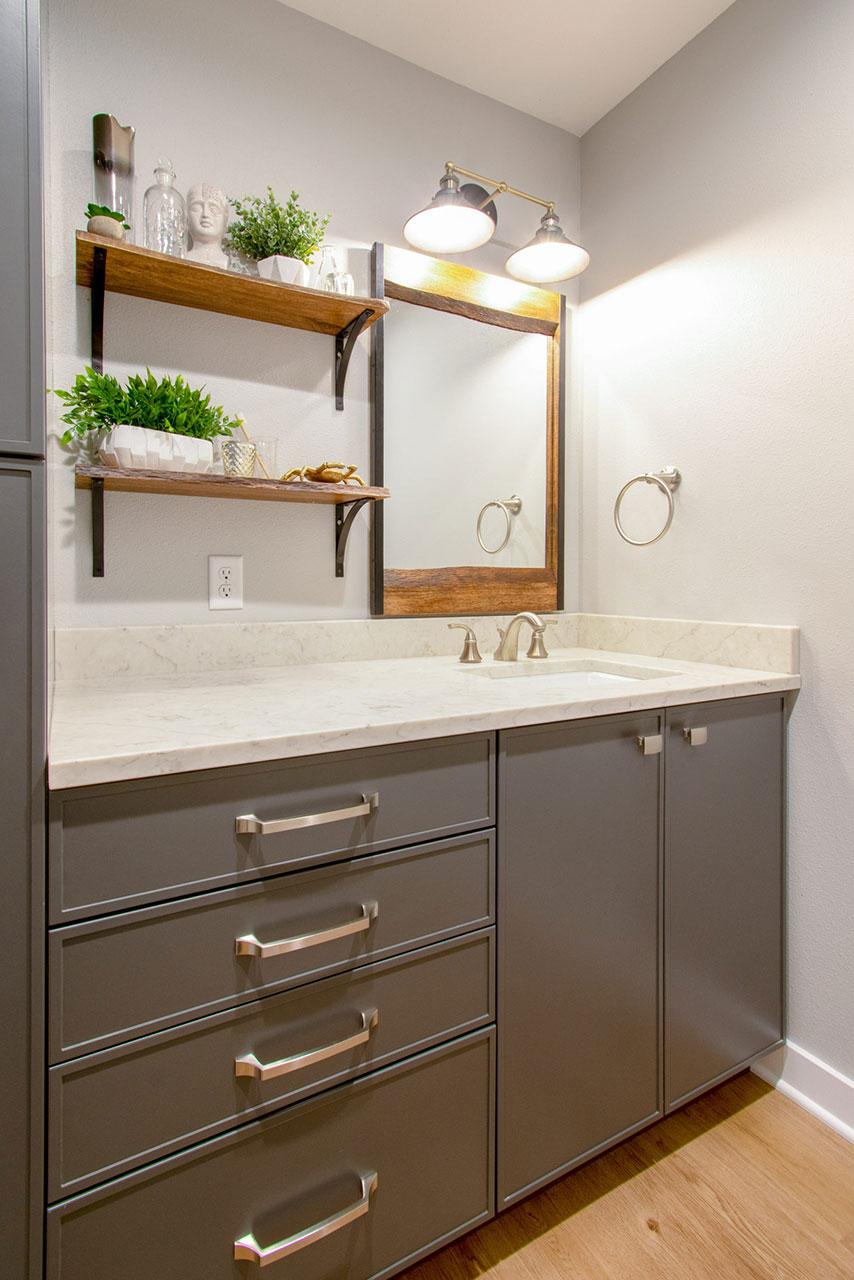 Hallway bathroom with gray vanity and open shelving