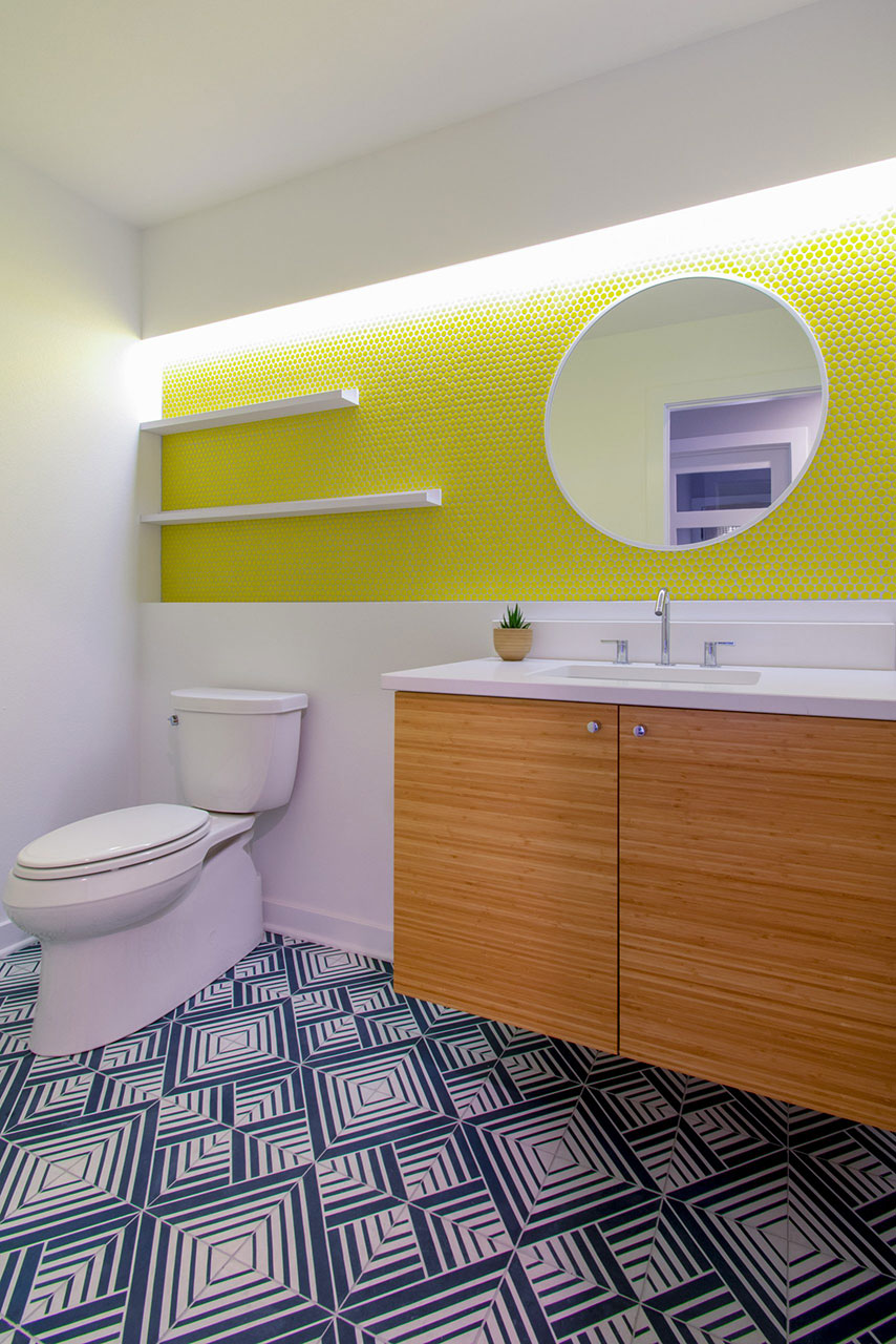 Modern powder room with yellow penny tile wall, open shelving, bamboo floating vanity and blue pattern cement tile floor
