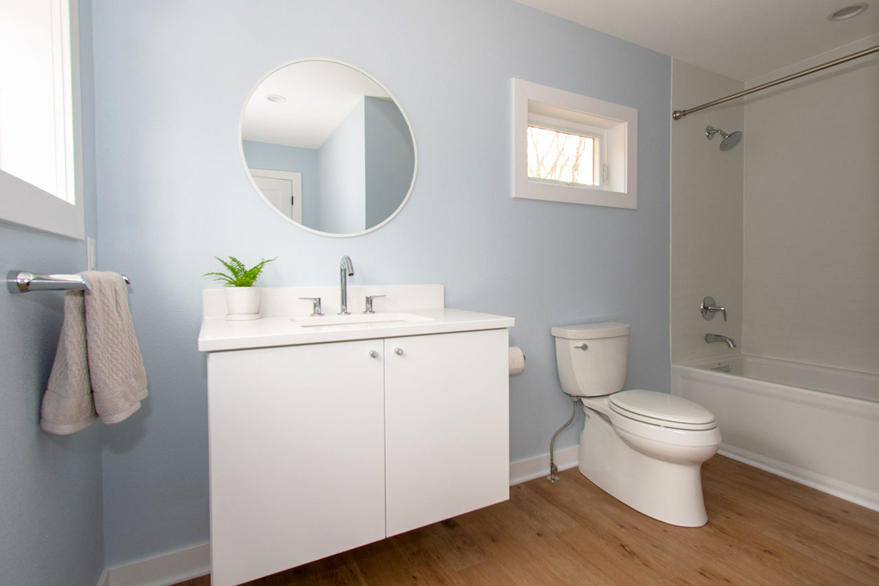 Contemporary bathroom with floating white vanity and round mirror